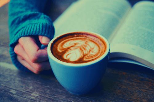 カフェで読書をしながらコーヒーをすする画像